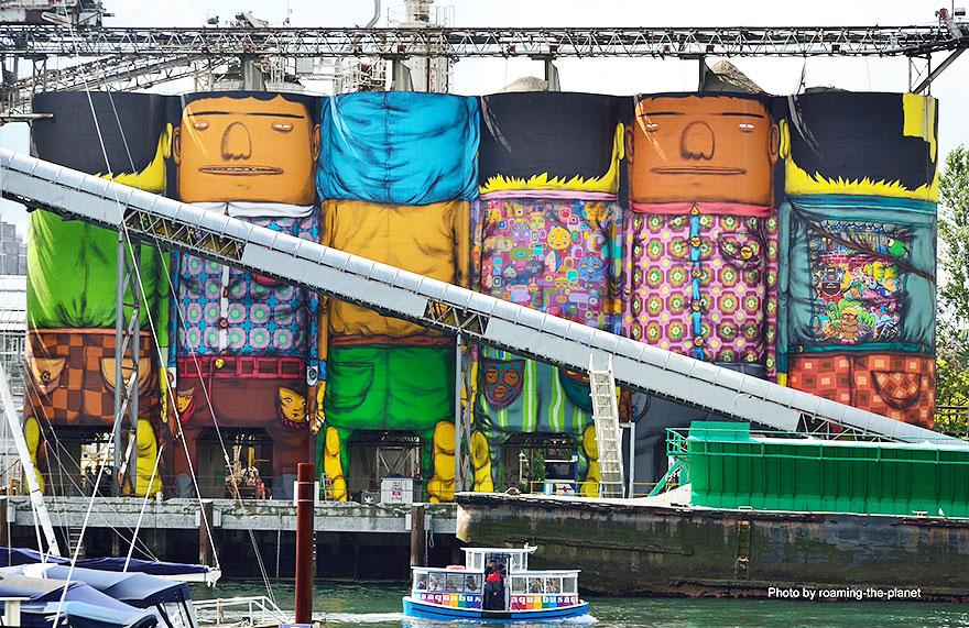 نمای نقاشی شهری غول پیکر سیلو ها از داخل بندر و قایق ها